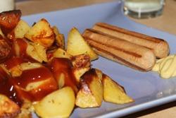 картошка под соусом с сосисками на тарелке