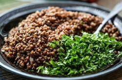 гречневая каша с зеленью в тарелке