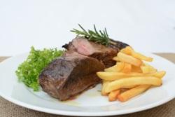 кусочк мяса с картошкой на тарелке